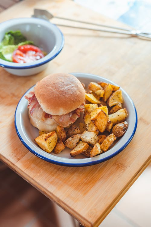 Appetizing hamburger with fried potato on plate