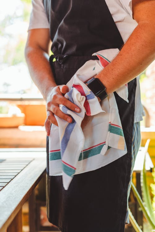 Crop unrecognizable male worker in apron and wristwatch cleaning hands with towel standing near table