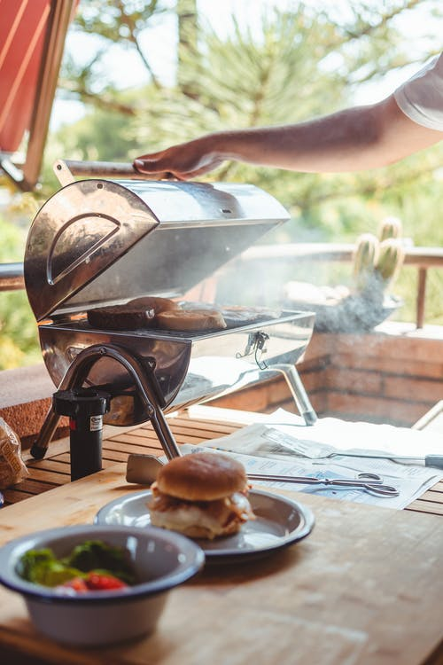 Crop anonymous male opening barbecue grill with fried bread for preparing burgers in nature
