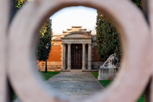 View through hole of gate on stone library with columns near sculpture in park