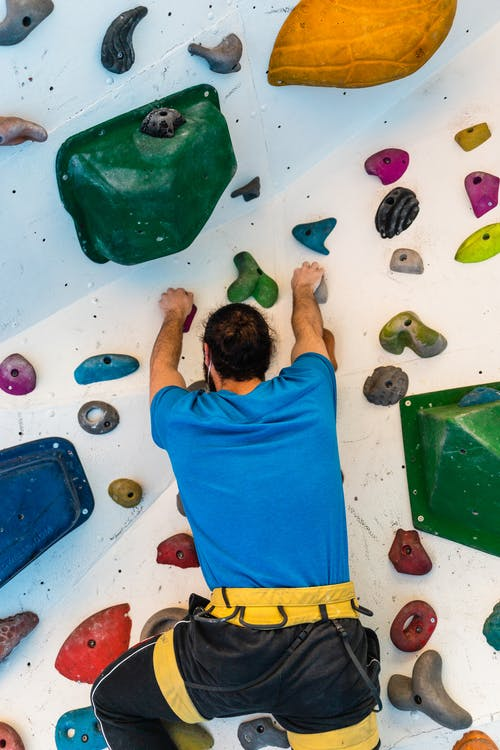 Strong climber ascending artificial boulder wall