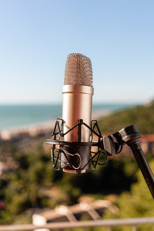 Microphone on tripod against hill and sea