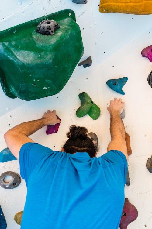 Unrecognizable climber ascending artificial rock