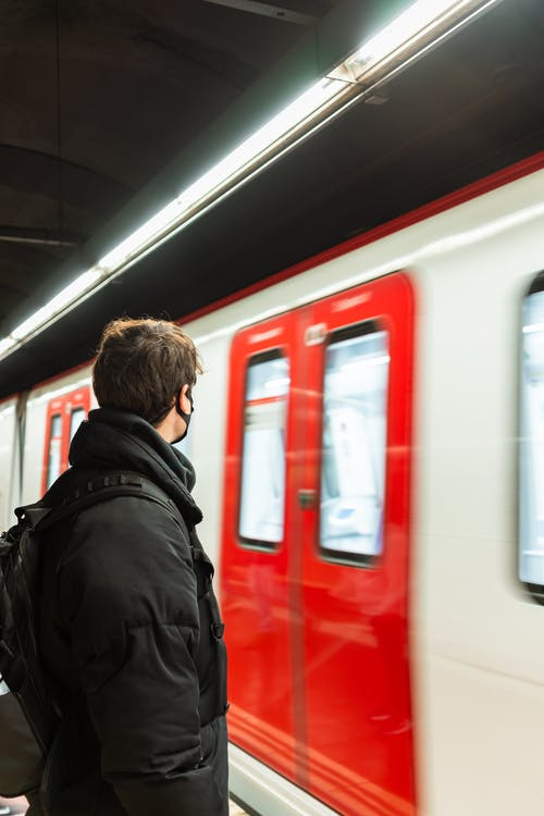 Anonymous man standing on subway station near train