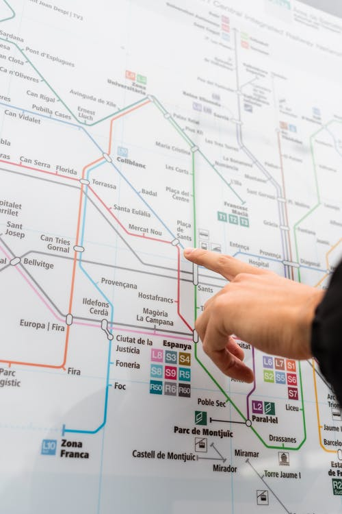Unrecognizable person pointing at map of metropolitan station with various colorful underground lines while choosing route for ride on street