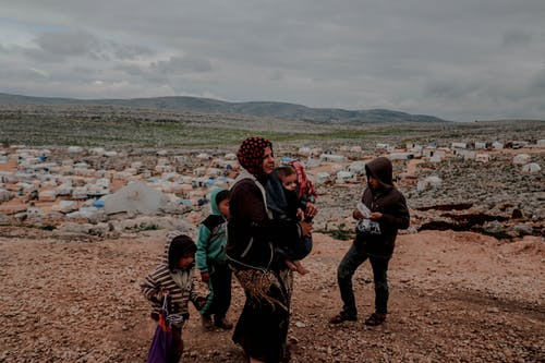 Poor ethnic woman with toddler in arms and kids near settlement surrounded with mountains under cloudy gloomy sky