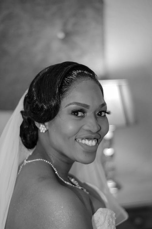 Cheerful black woman with elegant hairstyle in wedding dress