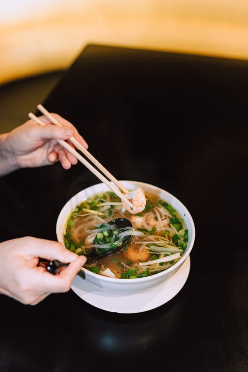 Person Holding White Ceramic Bowl With Noodles