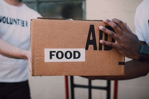 People Handing Over a Brown Box with Label