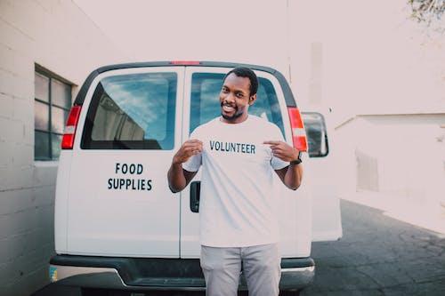 A Man Standing Beside a White Van