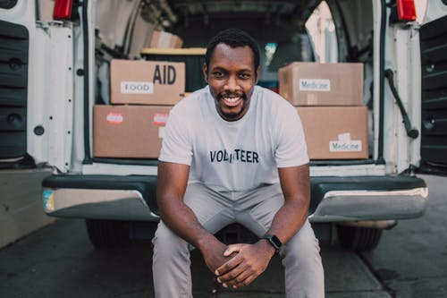 A Man Sitting at the Back of a White Van