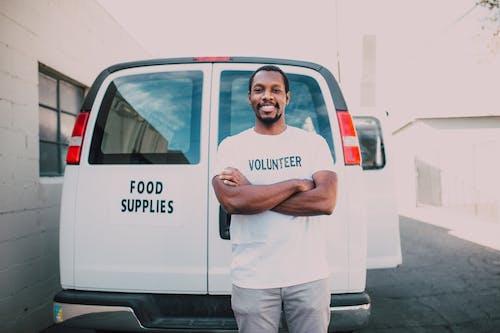 Man in White Crew Neck T-shirt Standing Beside White Van