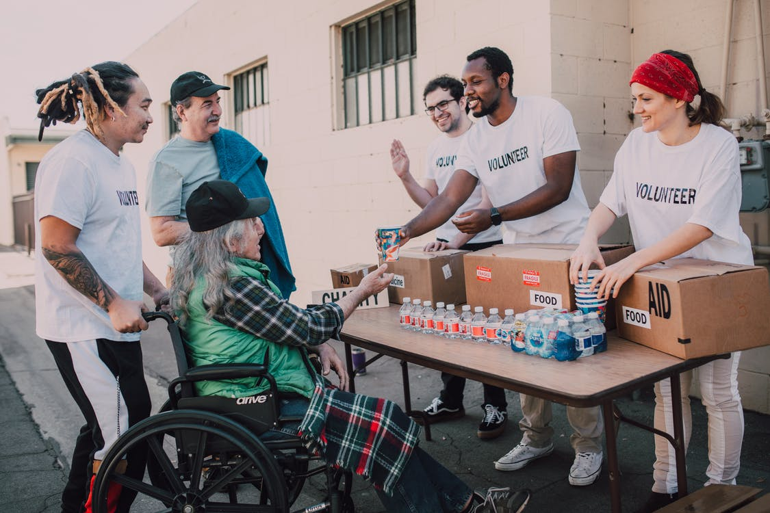 Man in White Crew Neck T-shirt Sitting on Black Wheelchair