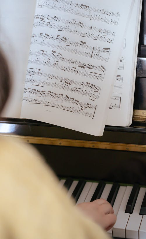Anonymous female musician playing piano near music book in room