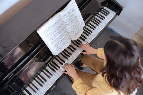 Woman in Yellow Long Sleeve Shirt Playing Piano