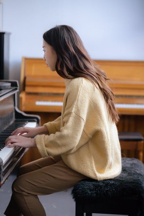 Side view of unrecognizable female pianist in casual outfit sitting on pouf while playing music on piano in bright room
