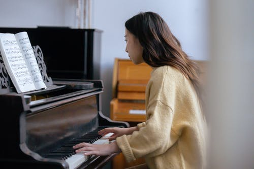 Side view of young female musician in warm sweater sitting in light room while practicing melody on piano with music book with notes