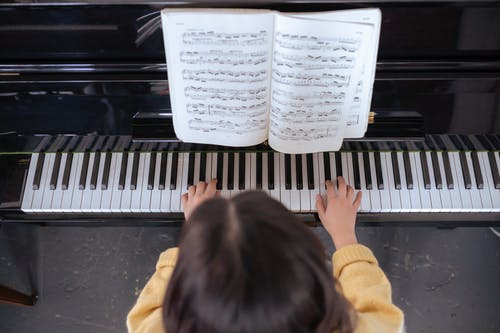 Faceless lady practicing on piano near music book in room