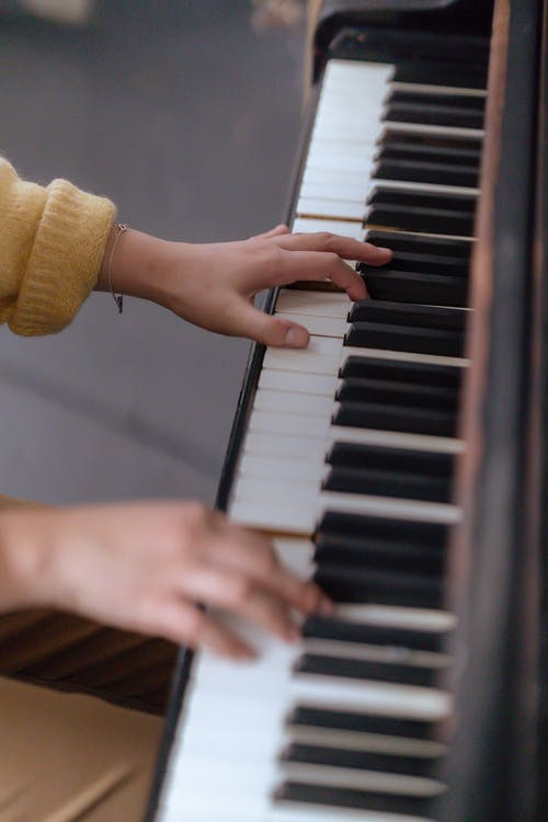 High angle of crop anonymous female musician in casual outfit playing on piano in bright classroom