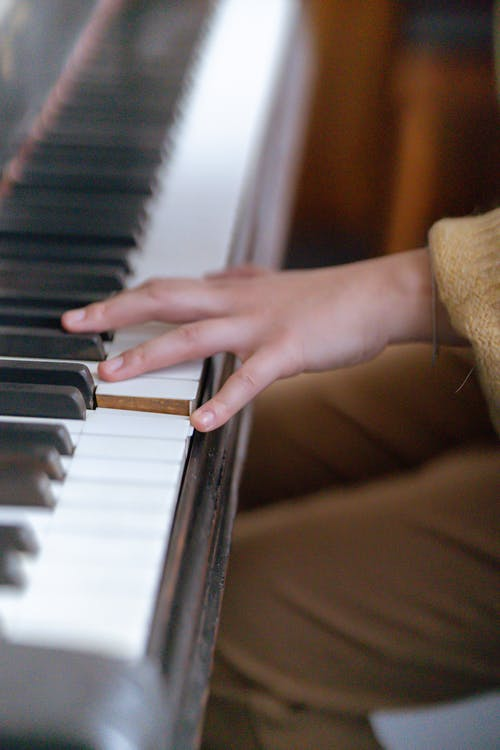 Unrecognizable female musician playing on piano in classroom