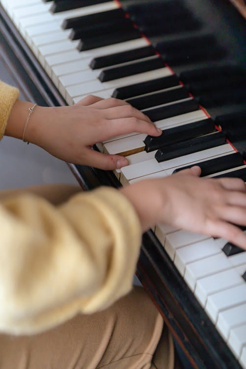 High angle of crop faceless woman in casual clothes practicing music on piano while sitting in bright room