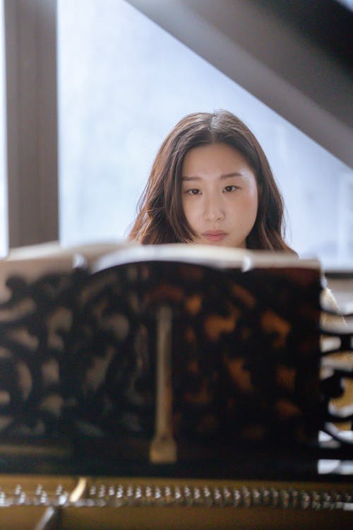 Ethnic female musician playing piano in classroom