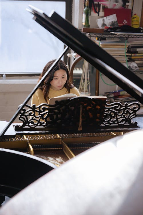 Concentrated young ethnic lady playing on piano with music book in bright classroom near shelves with decorations and books