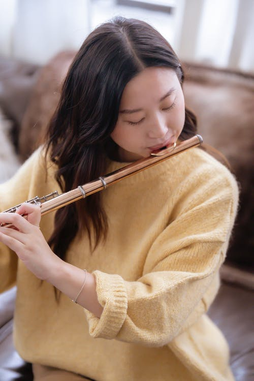 Young Asian woman in casual clothes practicing melody on flute while sitting on couch in bright room