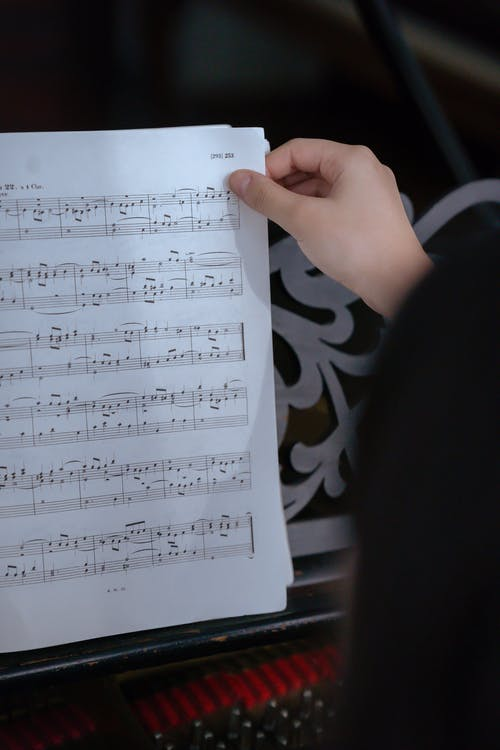 Crop unrecognizable female musician turning page of music book with notes near piano in light classroom