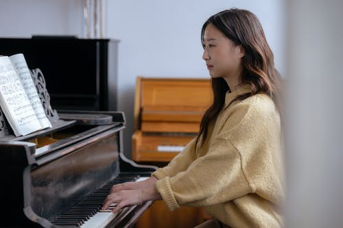 Side view of Asian woman in casual clothes practicing music on piano while sitting in bright classroom