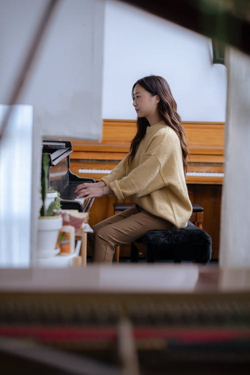 Asian lady practicing melody on piano in classroom