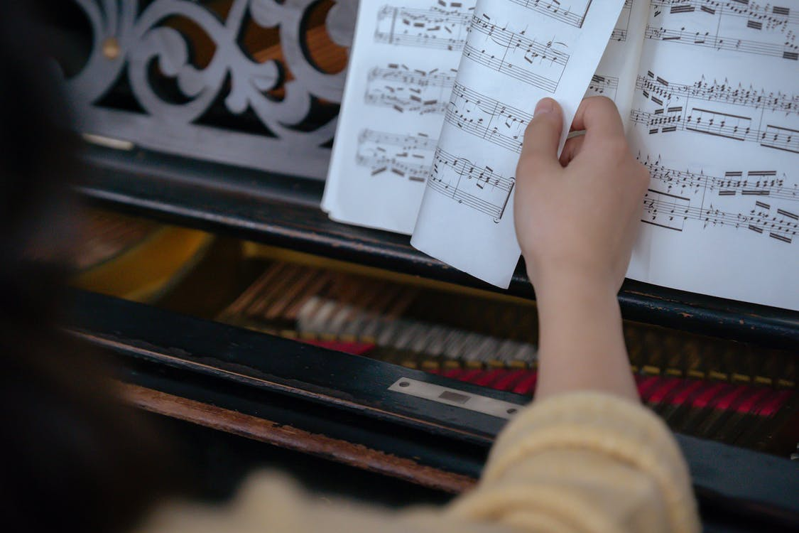 Unrecognizable woman turning page of music book near piano