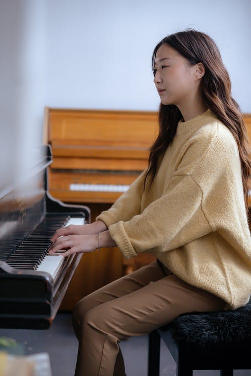Asian female musician playing piano in classroom