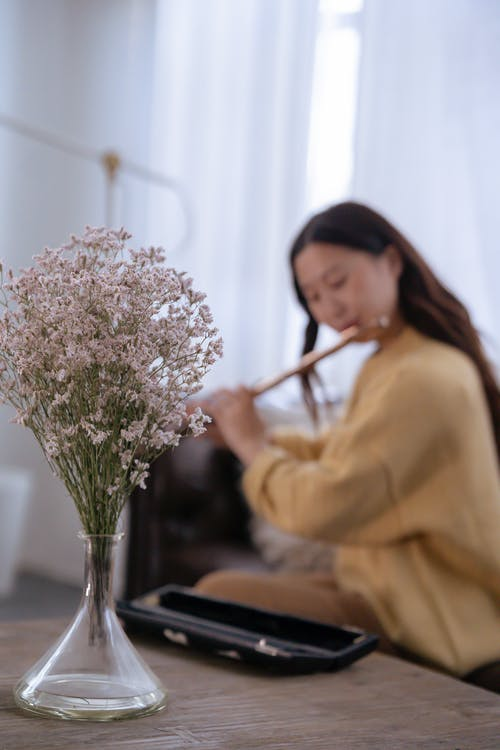 Bouquet of flowers on table near Asian woman playing flute