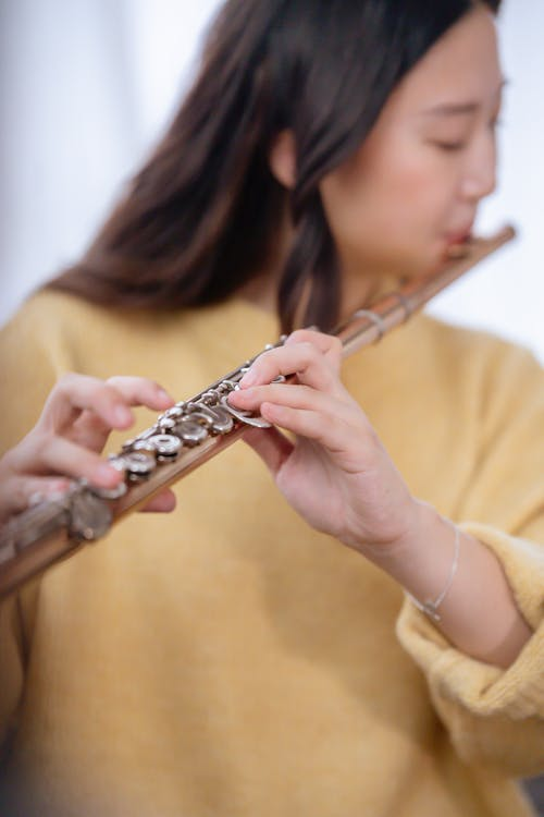 Crop young woman with long hair wearing soft knitted pullover pressing buttons of flute while playing classic musical instrument