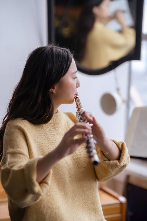 Side view of concentrated Asian woman in yellow clothes reflecting in mirror while playing flute