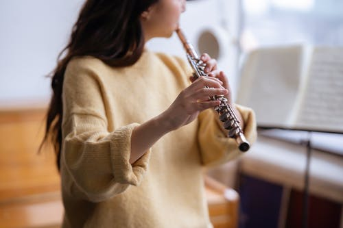 Crop talented lady in casual outfit looking into music book placed near window while playing musical instrument in studio with piano on blurred background