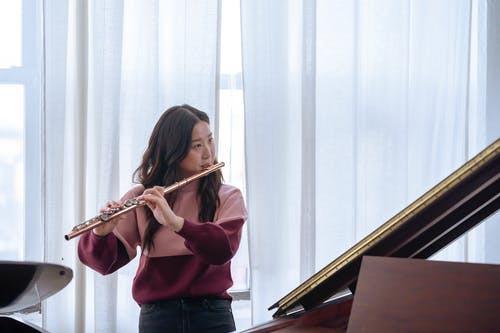 Focused Asian musician in casual clothes playing flute while standing near grande piano in daytime