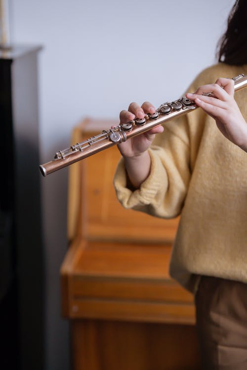 Crop unrecognizable woman playing flute while learning in music studio against piano in daytime while