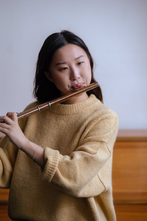 Young Asian lady in warm sweater playing flute in light classroom near wooden piano