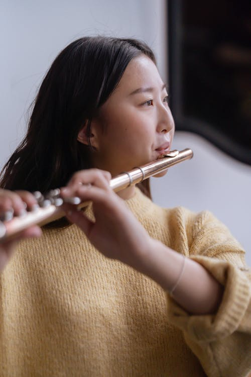 Thoughtful young Asian lady in warm sweater playing on flute in light classroom