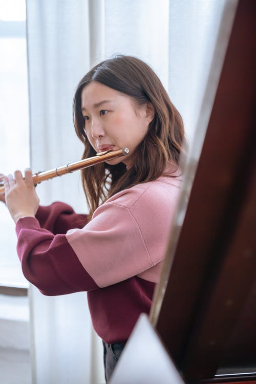 Pensive young Asian lady in warm sweater playing on flute in light classroom near window with curtains