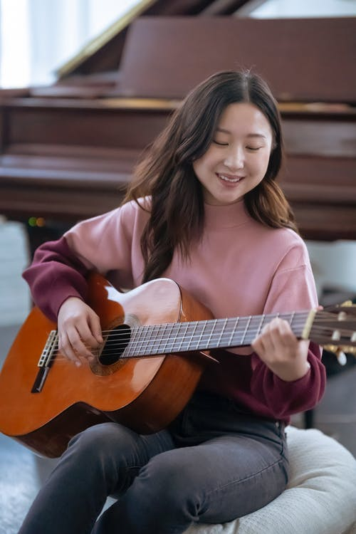 Smiling Asian female musician in casual wear playing acoustic guitar while sitting near piano during rehearsal at home in light room