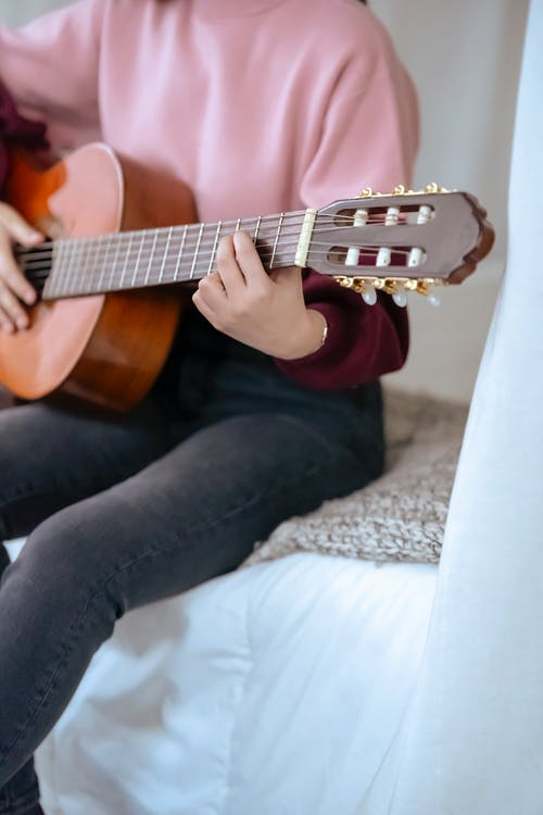 Unrecognizable female musician playing acoustic guitar while sitting on comfortable bed in cozy bedroom with white curtains during rehearsal at home