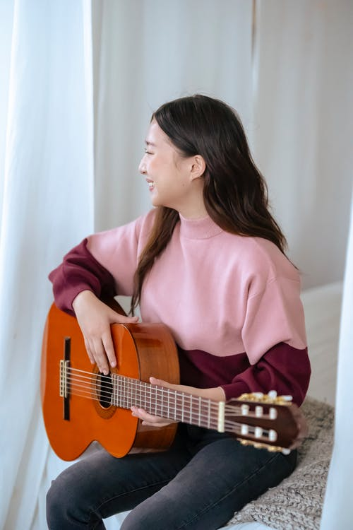 Smiling Asian woman with guitar on bed