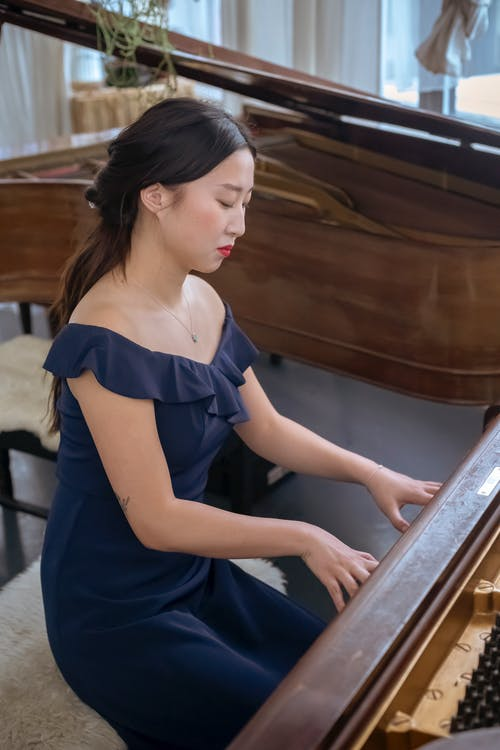 Side view of talented Asian female musician in elegant dress playing piano while rehearsing in light room during rehearsing at home