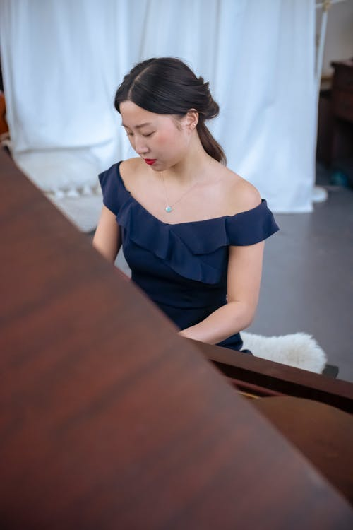 Concentrated skilled Asian female with makeup wearing stylish dress playing classic piano while rehearsing in light room with white curtains