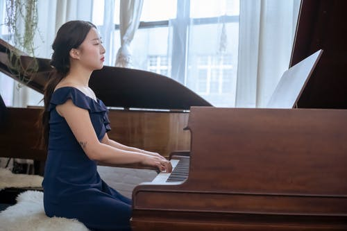Side view of skilled Asian female in elegant outfit performing melody piano while sitting in light room with musical instruments