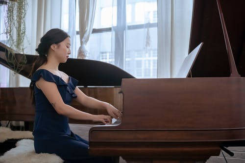 Focused Asian woman in elegant dress playing piano