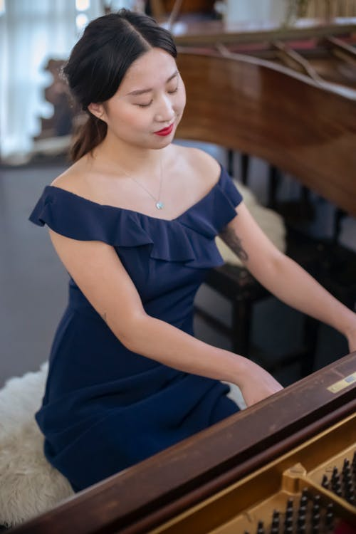 Positive talented Asian female pianist with makeup in elegant dress playing melody on instrument while rehearsing in room at home